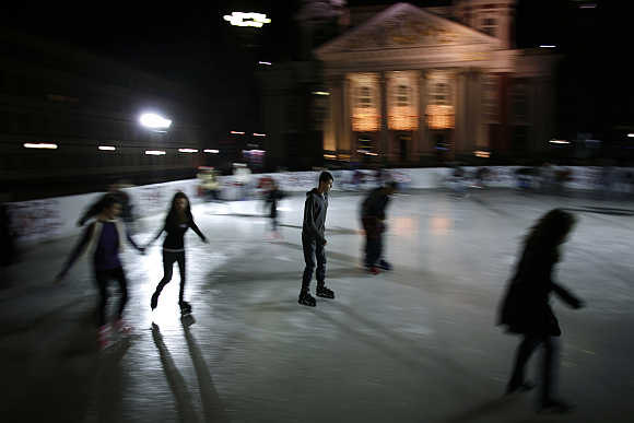 People skate in an outdoor ice rink in front of the National Theatre in central Sofia.