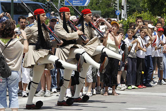 Tourists watch a performance of the Changing of the Guard Ceremony in front the Greek Parliament Building in Athens.