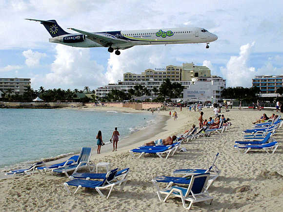 A small jet flies over Maho Beach in Sint Maarten.