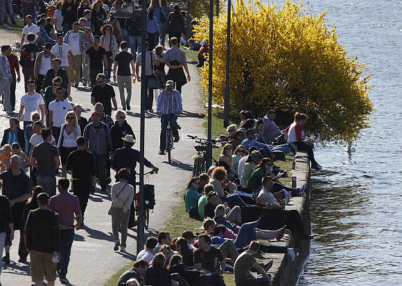 Pedestrians enjoy the sun and warm weather during a walk along the river Main in Frankfurt.