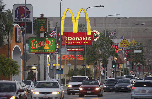 Cars drive past the signs of restaurants along a busy street in Los Angeles.