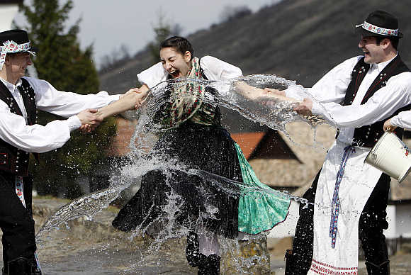 Men throw water at a girl as part of traditional Easter celebrations in Holloko, 100km east of Budapest.