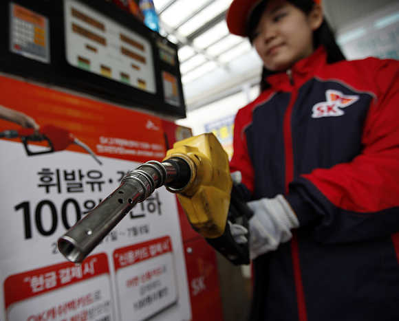 An employee holds a pump to refill a car in Seoul, South Korea.
