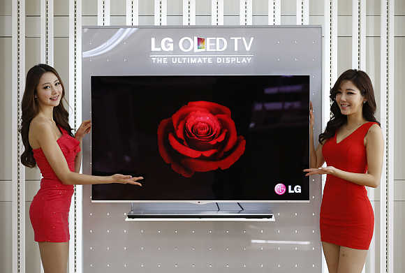 Models pose next to a LG Electronics' OLED television in Seoul.