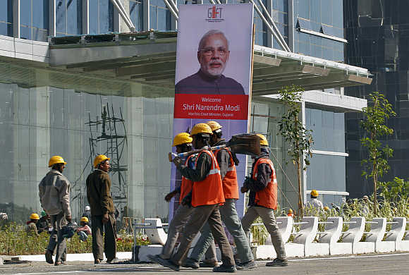 Workers walk past a poster of Gujarat Chief Minister Narendra Modi in Gandhinagar.