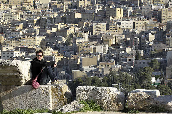A tourist looks towards a mountain while sitting at the Amman Citadel.