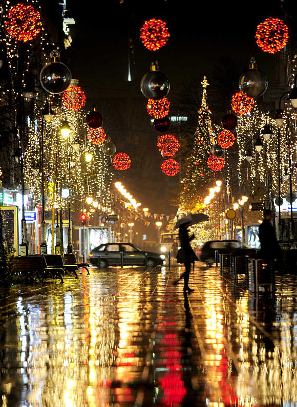 A woman walks near trees illuminated with Christmas lights in Skopje.