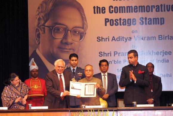 President Pranab Mukherjee, with Kapil Sibal on left and Milind Deora on right, released postage stamp on Aditya Vikram Birla.