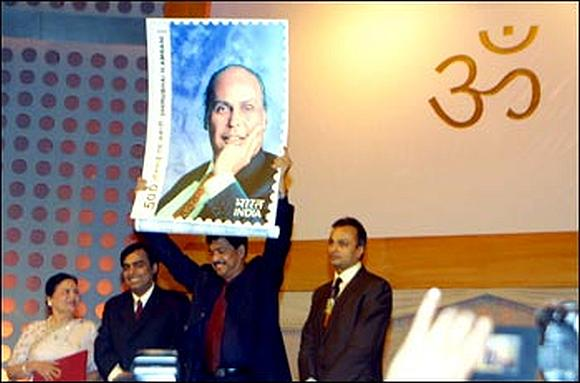 Late Pramod Mahajan holding a stamp commemorating Dhirubhai Ambani. He is flanked by Dhirubhai's sons Anil (right) and Mukesh, and wife Kokilaben (far left).