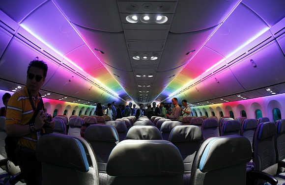 Economy-class cabin of the Boeing 787 Dreamliner is lit with rainbow coloured LED lighting during an media tour of the aircraft ahead of the Singapore Airshow.