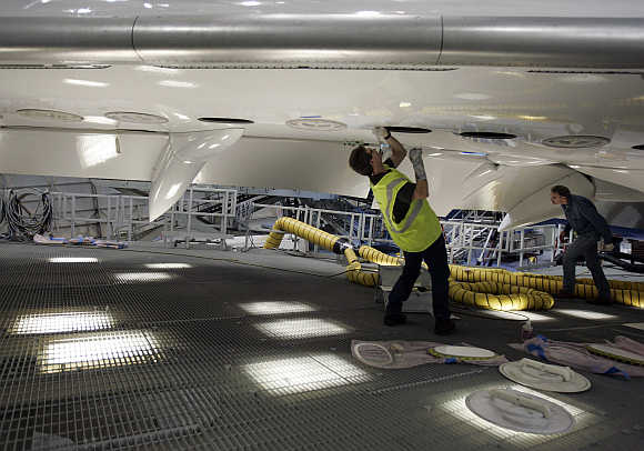 Boeing aircraft maintenance technician Bill Lucyk works on the underside of the first 787 Dreamliner as it's readied for it's first test flight at the Boeing company's Everett plant.