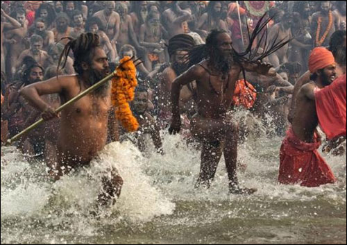 Naga Sadhus take a dip during the first Shahi Snan (grand bath) at the ongoing Kumbh Mela in Allahabad on January 14, 2013.
