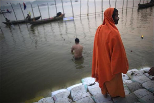 A Sadhu stands on the banks of the river Ganges.