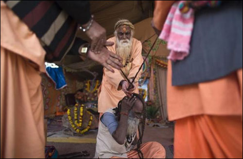 A Sadhu receives help from another in tying his hair on the banks of the river Ganges.