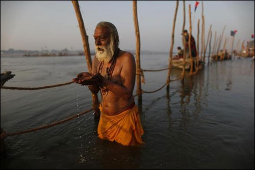A devotee prays before taking a dip in the waters of the holy Ganges.