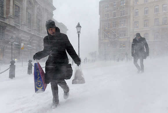 A woman struggles against wind and drifting snow in Stockholm.