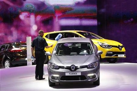 A worker cleans a Renault car at the European Motor Show in Brussels.
