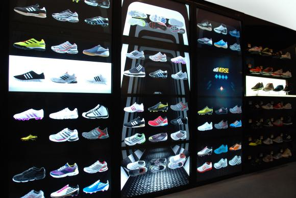 Images of shoes displayed on a virtual wall at an Adidas store.