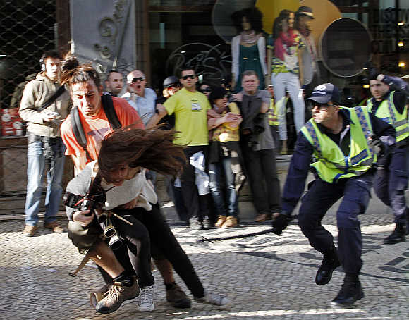 A policeman strikes AFP photojournalist Patricia Melo during the Portuguese general strike in Lisbon.