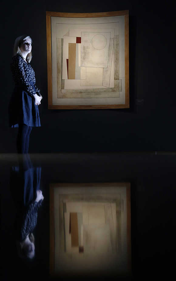 A employeee poses with Ben Nicholson's 'October 1949 (composition-Rangitane)' at Christie's auction house in London.