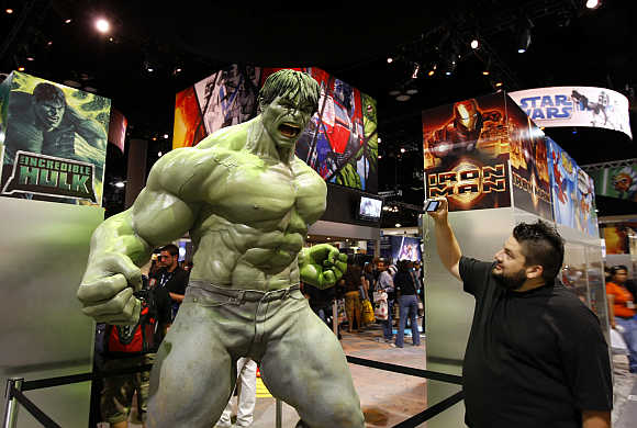 An attendee takes a picture of a life size Incredible Hulk in San Diego, California.