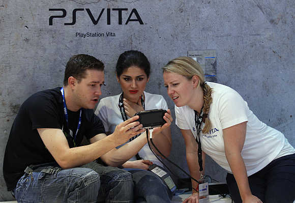 Visitors play with Playstation PS Vita at the Sony Playstation exhibition stand in Cologne, Germany.