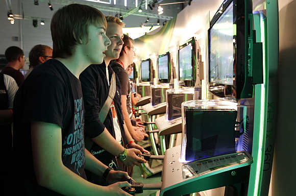 Visitors play the Xbox at the Microsoft exhibition stand in Cologne, Germany.