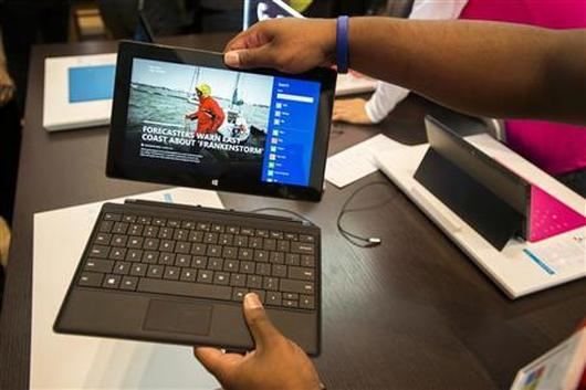 Sales staff demonstrate the Microsoft Surface during the opening of Microsoft's retail store in New York's Times Square.
