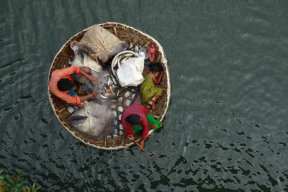 A fisherman arranges a fishing net as his wife paddles their boat in the waters of the Periyar river, Kerala.