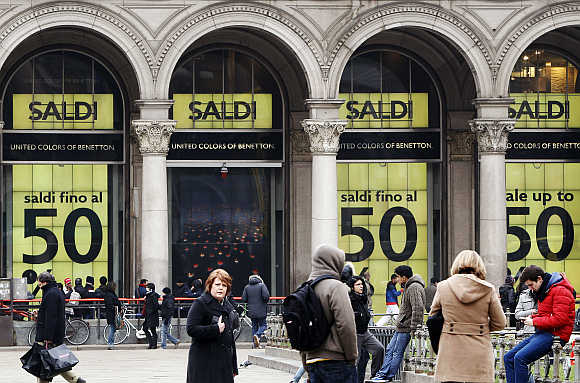 People walk in front of a department store having a sale in downtown Milan.