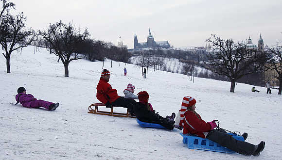 People slide down a snow covered Petrin hill in Prague.