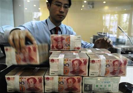 An employee counts Chinese yuan banknotes at a bank in Hefei, Anhui province.