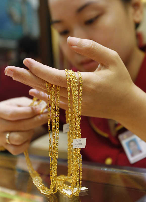 An employee looks at gold jewellery at a shop in Hanoi, Vietnam.