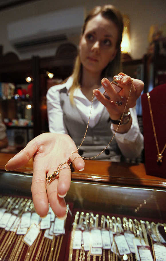 An employee displays gold jewellery in Russia's Siberian city of Krasnoyarsk.