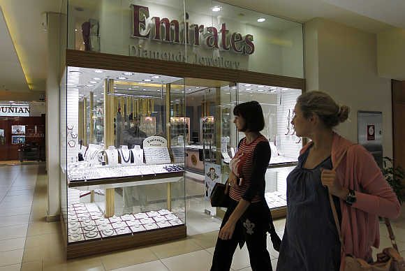 Women walk past the Emirates Diamonds shop at Gold and Diamond Park, a shopping mall specialised in gold and diamond retailing, in Dubai.
