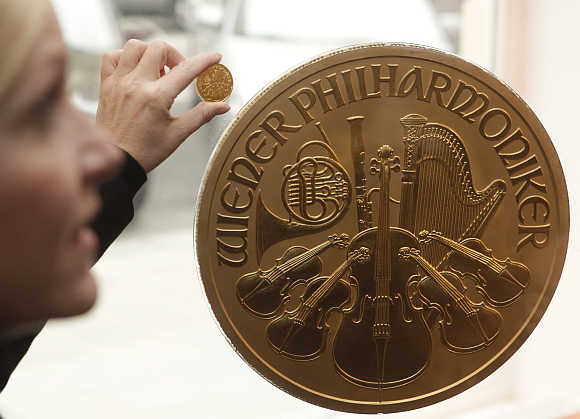 A woman displays a small gold coin next to Europe's largest gold coin in a shop in Vienna, Austria.