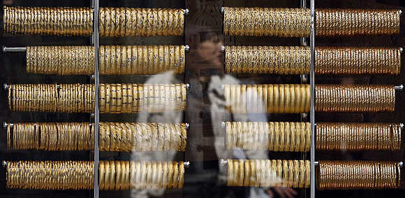 A woman is reflected on the window of a jewellery shop where gold bangles are on display in Istanbul, Turkey.