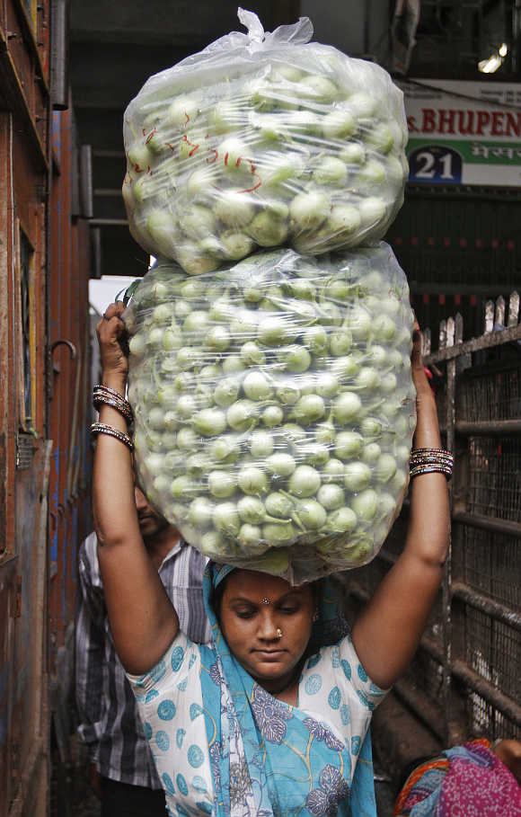 A woman carries bags of white brinjal at a wholesale vegetable market in Ahmedabad.