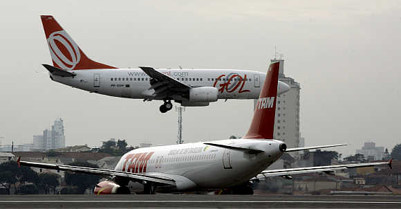 A TAM airlines Airbus A320 taxies to take off as a Gol airlines Boeing 737 lands on the runway at Sao Paulo