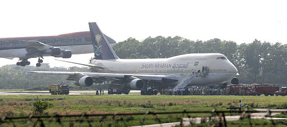 A Bangladeshi aircraft lands near a Saudi Airlines 747 plane at Dhaka's Zia International Airport.