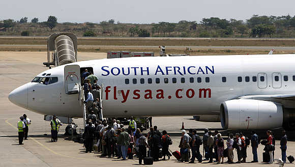 Passengers board a South African Airways Boeing 737 aircraft at the Kamuzu International Airport in Lilongwe, Malawi.