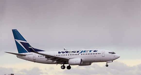 A WestJet airplane comes in for a landing at Calgary International airport, home of Canada's WestJet Airlines in Calgary, Alberta.