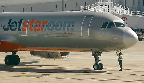 Jetstar ground staff closes a panel at Melbourne airport in Australia.