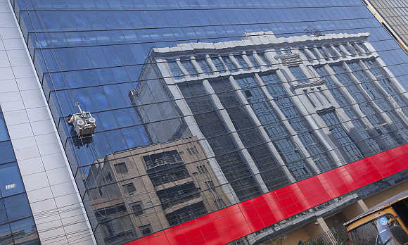 A window cleaner in a gondola cleans glass facade of a building in a business district in Karachi.