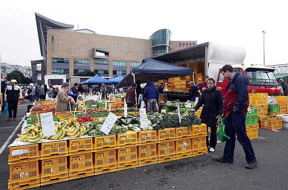 People buy fruits at a market in front of the Te Papa Museum in Wellington.