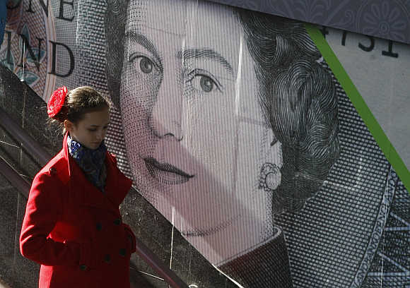 A woman passes by an outdoor advert with an image of the British pound bank note in central Kiev, Ukraine.