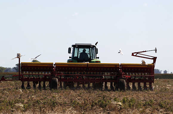 A worker drives a tractor pulling a sowing machine to plant soybeans in Estacion Islas, Buenos Aires, Argentina.
