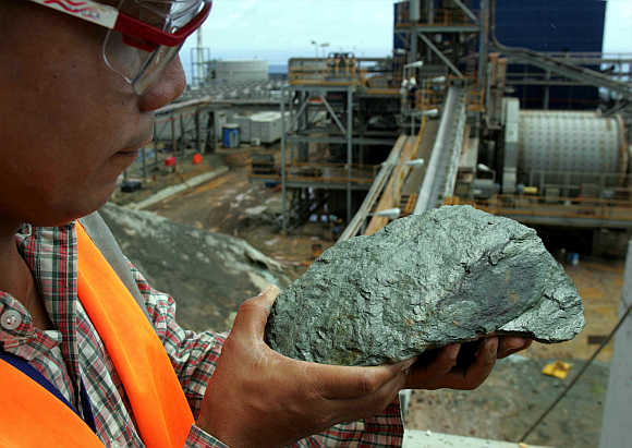 A mining engineer examines a mineralized ore containing copper and zinc in Lafayette Mining's open pit at Rapu Rapu island in the Philippines.