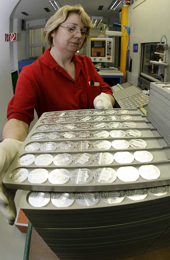 A worker at the Austrian Mint holds a tray of silver Vienna Philharmonic Bullion coins at the Mint's headquarters in Vienna, Austria.