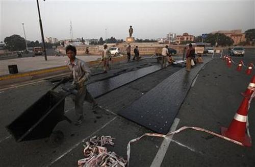 Labourers work at a road construction site outside Ambedkar memorial park in Lucknow.